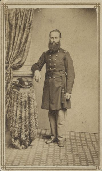 Full-length carte-de-visite portrait of Dr. Christopher Ruby Blackall, 33rd Wisconsin Infantry, standing in his uniform with his hat on a pedestal.