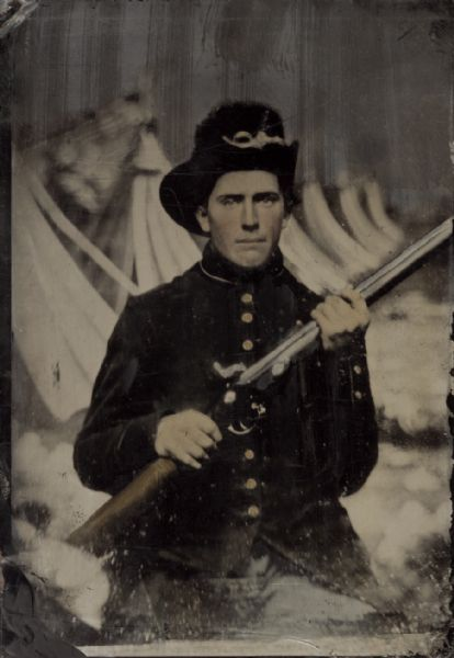 Tintype and hand-colored portrait of John Hodges (who lived in La Fayette), Company I, 28th Wisconsin Infantry, holding his musket. He enlisted on August 21, 1862 and was mustered out of service on August 23, 1865. The background appears to be a painted depiction of a row of tents.