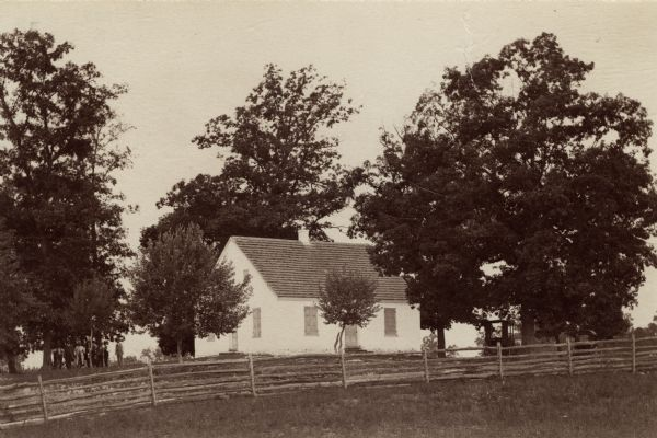 Site of the Battle to Antietam, The Dunker Church. A group of men stand among trees on the left. Horse-drawn carriages are under trees on the right.