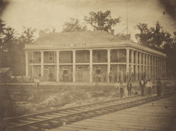 View across railroad tracks of men standing in front of and around Osborne House, a large building with columns and a second-story porch.
