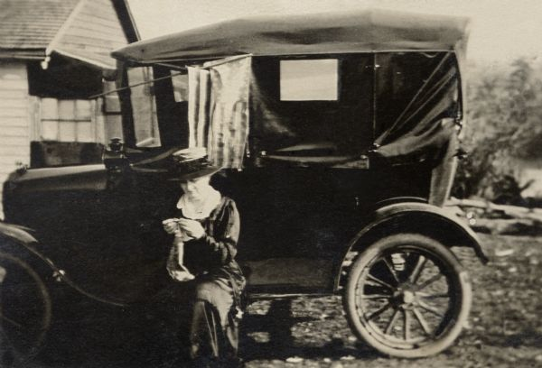 Katherine (Kate) Quinney, Richard Quinney's great aunt, crocheting while seated on the running board of a Ford Model T in the yard of her family's farm.