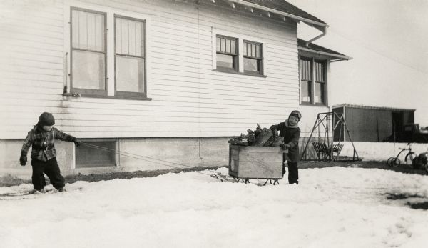 Winter scene with young Richard and Ralph Quinney hauling firewood on a sled through the snow past the farmhouse.