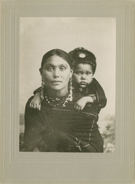 Quarter-length studio portrait of a woman in Ho-Chunk regalia wrapped in a blanket, with a child on her back. The child is wearing a fur hat, and the woman is wearing long earrings and a necklace. They are posing sitting in front of a painted backdrop. Clara Kingsley (Big) Blackhawk (KeesKawWinKah) carries her son Andrew John (Big) Blackhawk (WaConChaHoNoKah) on her back. Using a shawl as a back sling was a common way to carry infants in this period.