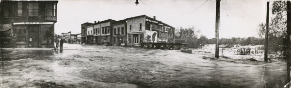 "A panoramic view of Black River Falls flooded streets, possibly taken during the flood of 1911. Three men are standing on the sidewalk next to the ""Tollack & Son"" storefront on the left street corner."
