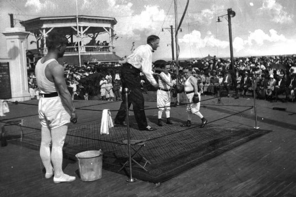 Spectators watch as two dwarfs box in a ring at Midland Beach.  A raised pavilion stands in the background.