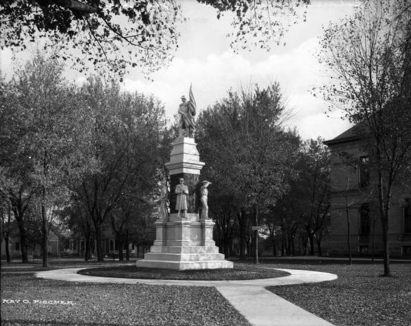 A civil war soldiers' monument stands in on the courthouse ground surrounded by a circular walkway and trees.  Several buildings are visible behind the monument.