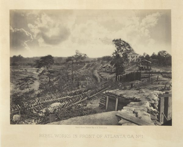 View looking out from one of the Confederate defenses around the outside of the city. Wooden palisades surround the earthworks. Houses and other buildings in the background are heavily damaged. Plate 39