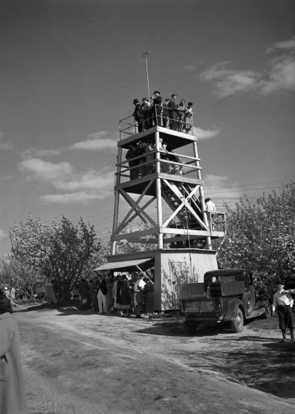 View across road of an observation tower overlooking extensive apple orchards, a tourist attraction in season. Many people are standing below the tower where a snack shop is located beneath an awning. Many people are crowded on the stairs waiting to get to the top of the tower. A truck is also parked nearby.