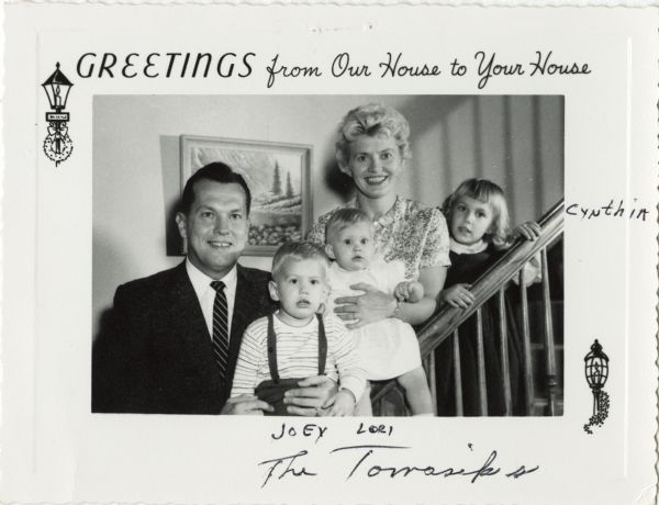 "Photographic holiday greeting card of a family posed on their staircase. A father, mother, two daughters and one son are pictured. At top is the text ""Greetings from Our House to Your House'."