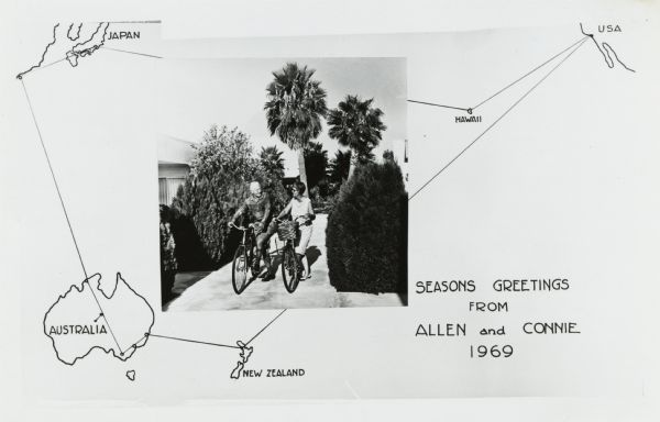 "Photographic holiday postcard of a couple on their bikes in a driveway. Shrubs and palm trees surround them. A map of the Pacific Ocean is in the background. with the route of their vacation trip indicated on it. The text reads: ""Seasons Greetings From Allen and Connie, 1969""."