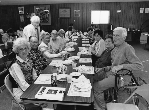 """At St. Theresa's parish hall our regulars are joined by ""Buddy"" Ruecker's friend Kitty Rogers & her mother Hilda Deamer (next to Ralph). Lucille Lux is at the left. A two-piece Cod plate was priced at $5.00."""