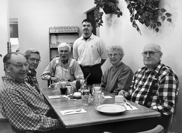 """Fish Fries are very reasonable at the Back Street Cafe. Red Fish (similar to Perch) are only $4.95. A large glass of Slice is 45¢. Our waiter is Brock Cotter."" From left to right; Rudy Heinecke, Ralph ""Buddy"" Ruecker, Ralph Widmer, Brock Cotter, Shirley Widmer, and John Bodden."