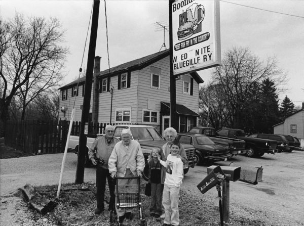 """The Boondocks is just North of Mayville on City. Tr. V. Carly & Parker Hren are our guests."" The restaurant sign reads, ""best fish fry in the country."" From left to right; John Bodden, Ralph Widmer, Carly Hren, Shirley Widmer, and Parker Hren."