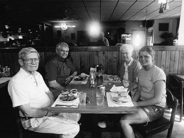 """Brittany was the cook and waitress at Rusty's Pub-N-Grub."" From left to right: Ralph ""Buddy"" Ruecker, Carl Bernhard, Shirley Widmer, and Brittany. Jim Widmer's reflection can be seen in the mirror."