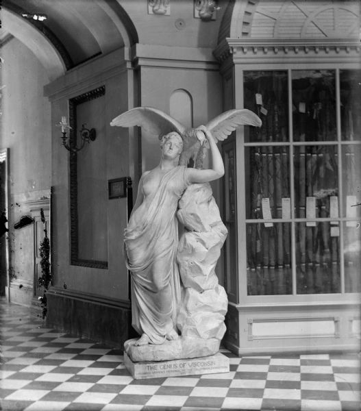 "The sculpture, ""Genius of Wisconsin"" by Helen Farnsworth Mears, displayed in the rotunda of the third Wisconsin State Capitol. On the right is a display case of Wisconsin Civil War flags; a gaslight fixture is on the wall to the left."