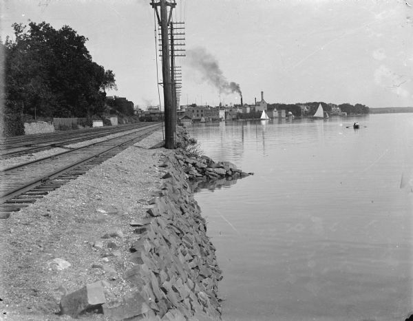 "A view east along the north shore of Lake Monona, with Madison's east side industrial area in the background. Tall utility poles and railroad tracks follow the shoreline. The Deering Harvester Company is identified by a sign painted on its wall; large letters on the roof identify the ""Advance Thresher Co."" The tallest tower right of the smokestack is part of the Fauerbach Brewery complex. The short domed structure on the shoreline is a gazebo which was also a part of the Fauerbach complex. Large private homes are seen on the far right.   There are people in a rowboat and in sailboats in the background."