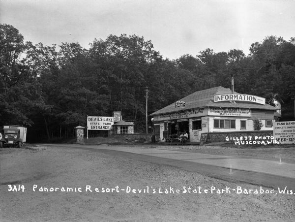 View of the entrance to Devil's Lake State Park. There is an information center offering gas, food, and Blatz beer. Two storekeepers and a boy sit on the porch. Over the entrance to the information center is a sign that says: Panoramic Resort Hotel and Cottages with Bath, Gas, Hot and Cold Water. Rates $1.00 and Up.""