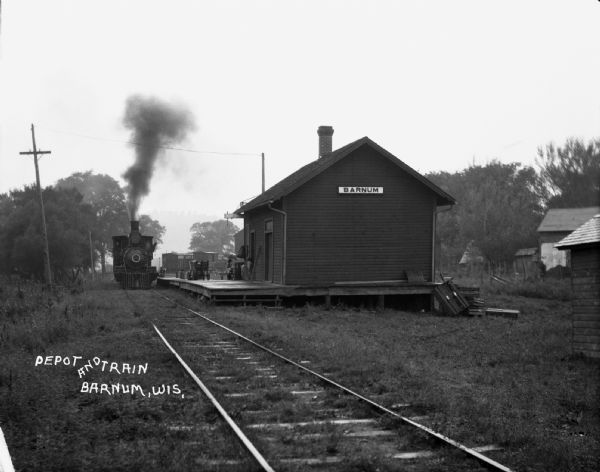 View from along railroad tracks of a train arriving at the depot. There is a child in the doorway of the depot, and a woman in the background is carrying an umbrella.