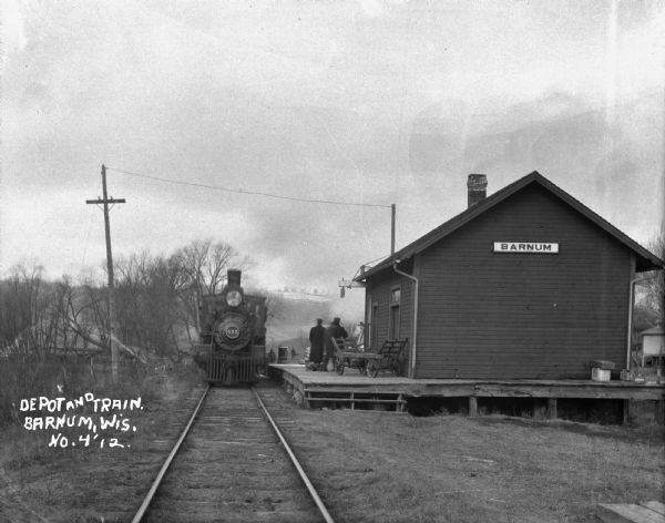 View down railroad tracks of a locomotive arriving at the Barnum Depot.