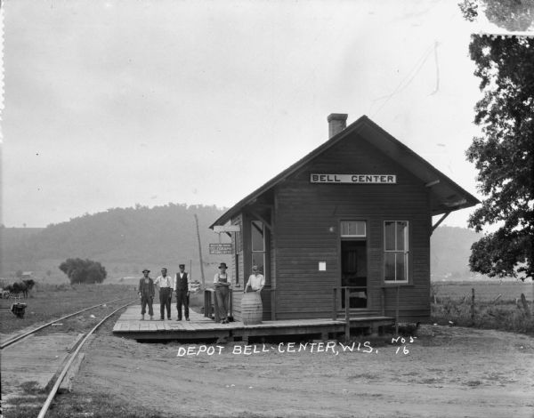 Exterior view of the Bell Center depot with five men posing on the platform.