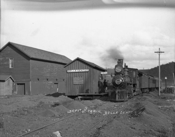 Exterior view of a locomotive at the Bell Center depot. Men stand on the platform.