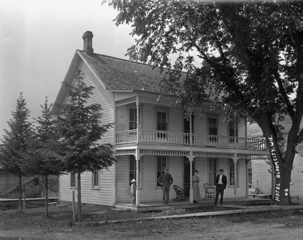 Exterior of a two-story hotel with two men, a woman and a child standing on the porch.