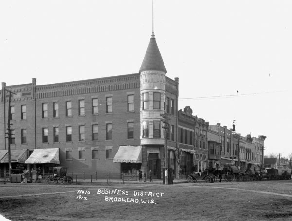 A main street intersection with many stores and shops. The stores include the Bank of Brodhead and A.J. Wagner's drugstore. Three boys stand at the corner. Cars and horses are parked along the curbs.