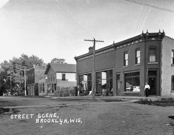 View across an intersection of a man standing at the corner entrance of an untitled shop. Down the sidewalk on the left a young boy leans over to talk with another boy sitting on the steps of a store with display windows. There are rolls of fencing mesh stacked in an alley along the side of the store.
