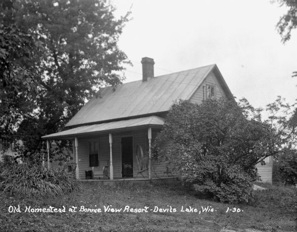 Cottage, with a spinning wheel on the porch, at the Bonnie View Resort near Devil's Lake.