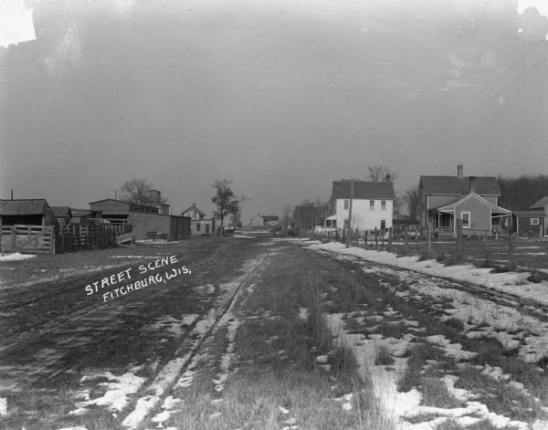View down dirt road towards the Lappley Bros. Lumber Yard. There are houses on the right and in the far background. There are horses and carriages parked along the edges of the street.