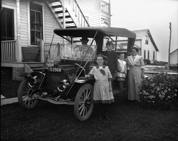J.L. McLaughlin and wife, two sons and one daughter posing around their Flanders automobile in front of their house. Outdoor stairs are leading up to the second-story of the house and there is a balcony in the back. A flowering bush is next to them on the right.