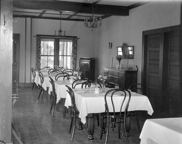 Dining room set with table settings. A mirror and a sideboard are next to the double doors on the right, and a Victrola is in the corner next to two windows. Chandeliers hang from the ceiling.