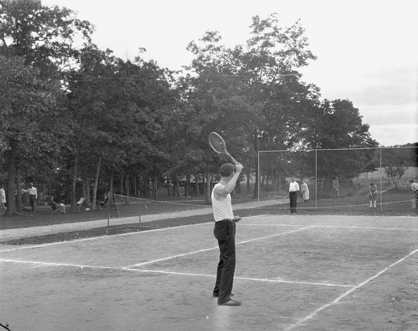 Two men playing tennis on the Birchcliff Hotel tennis court. Another group of guests are playing croquet on the lawn in the background. People relax on chairs under trees on the left.