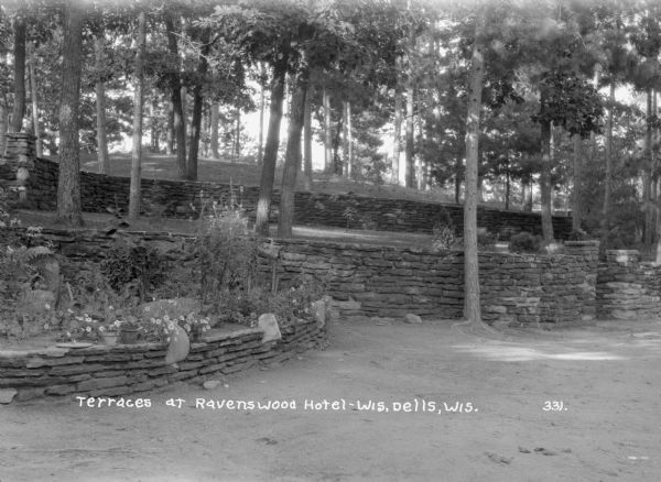 Stone terraces at the Ravenswood Hotel. In the foreground are flowers, some potted, in a raised bed. Two more stone walls are on the hill in the background, with trees on the lawn.
