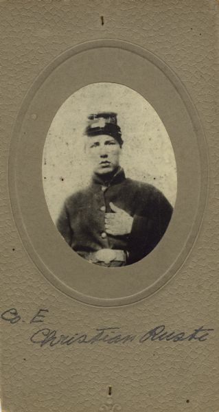 Waist-up oval studio portrait of Christian Ruste, a private in Company E, 15th Wisconsin Infantry in uniform. The following information was obtained from the Regimental and Descriptive Rolls, Volume 20: He resided in Blue Mounds, Wisconsin. On January 8, 1862, he enlisted at Camp Randall in Madison, Wisconsin and was mustered into service in Madison, Wisconsin on January 11, 1862, at the age of 17. He died on May 2, 1862, at Island No. 10 (Tennessee) of Typhoid fever.
