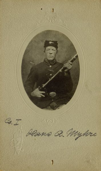 Waist-up seated oval studio portrait of Hans A. Myhre, a private in Company I, 15th Wisconsin Infantry in uniform holding a musket across his chest. The following information was obtained from the Regimental and Descriptive Rolls, Volume 20: He held residence in St. Laurence, Wisconsin. On December 9, 1861, he enlisted in Scandinavia, Wisconsin and on December 20, 1861, he was mustered into service in Madison, Wisconsin at the age of 21. He was mustered out of service with company on February 10, 1865, at Chattanooga, Tennessee.