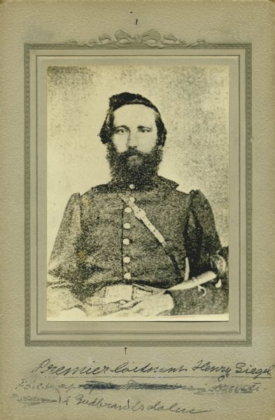 Waist-up seated studio portrait of Henry Siegel, a captain in Company A, 15th Wisconsin Infantry, in uniform, holding a sword across his lap. The following information was obtained from the Regimental and Descriptive Rolls, Volume 20: He resided in Chicago, Illinois. On September 27, 1861, he was enlisted as a first sergeant and mustered into service on November 15, 1861, in Madison, Wisconsin. On September 22, 1862, he was detached from the company to serve as the brigade commissary sergeant. On September 16, 1862, he was promoted to first lieutenant. On October 13, 1863, he was place in charge of a supply train to Stevenson, Alabama. On October 19, 1864, he was commissioned a captain. He mustered out with the company on December 20, 1864, at Chattanooga, Tennessee.