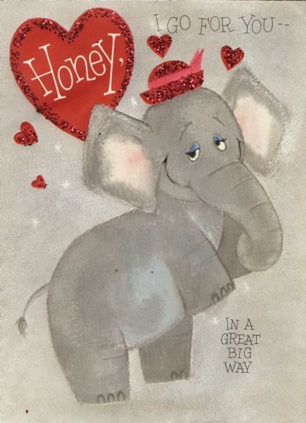 "Valentine's Day card with the image of an elephant. She is wearing a red hat with a pink bow and is standing up on her back legs. A red heart in the upper left corner says ""Honey,"" text on the right reads ""I Go For You —"" and below ""In A Great Big Way."" Red glitter is glued to her hat and the hearts in the background. The inside (not shown) is a large foldout, die cut face of an elephant with the text ""So Let's Be Valentines — OK?"" Offset lithography, embossed and die cut with glitter."