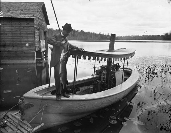 Steamboat on Long Lake owned by Lorenzo Newman of Chippewa Falls. It is anchored at Newman Peninsula on Long Lake near a wet boathouse. The boat was operated by steam and used as an excursion boat. It had cushioned seats, electric lights and a canvas canopy. In the background is the far shoreline of the lake.