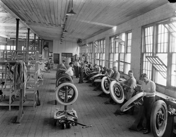 Elevated interior view of the Boone Tire Factory. Men are lined up along a wall with open windows. They are each using a stand to hold a wheel while wrapping a layer of canvas or rubber around the outside edge of the tire. Shelves on the right hold canvas and strips of rubber. Several other men stand between racks of tires, observing them. The room also contains machinery and shelving.
