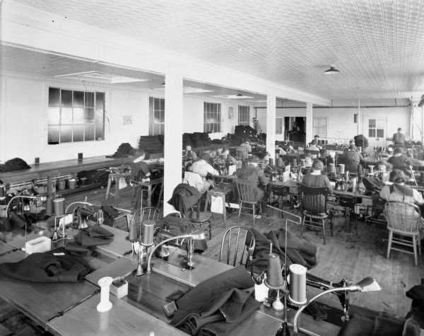 About twenty women sit at tables sewing on sewing machines in the sewing room of the Chippewa Woolen Mill.