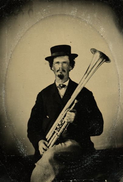 Tintype portrait of Joseph Smith of Evansville, Wisconsin, member of the 3rd Wisconsin Infantry band. He is seated wearing a suit and holds a tenor horn.