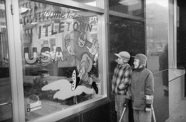 "Two young boys, one with Loftstrand-style crutches most likely due to polio, are looking at a window display. The Packers were about to play for, and would go on to win, their seventh title as World Champions of Pro Football. Text written on the window reads ""Welcome to Green Bay, Titletown U.S.A."""