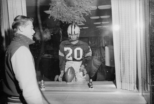 A teenage boy looks at a window display of a mannequin dressed up in a Packer uniform, as well as two small Packers bobble-head toys. The Packers were about to play for, and would go on to win, their seventh title as World Champions of Pro Football.