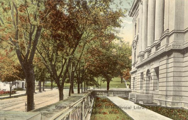 "Colorized postcard of the State Street entrance of the State Historical Library, now the headquarters building of the Wisconsin Historical Society. Bascom Hill is in the background. The text below reads ""State Street Entrance to Historical Library, Madison, Wis."""