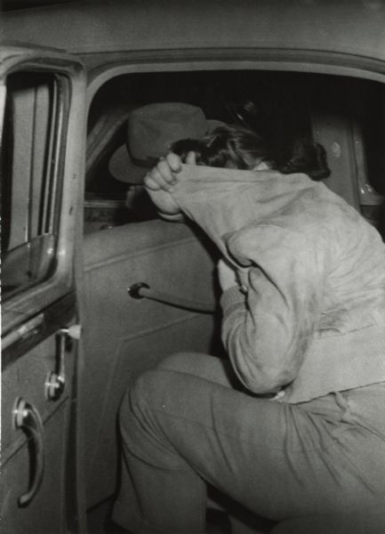 View of a woman as she was loaded into the agent's car after a raid at Rae's Blackhawk Bar. She is hiding her face in her coat.