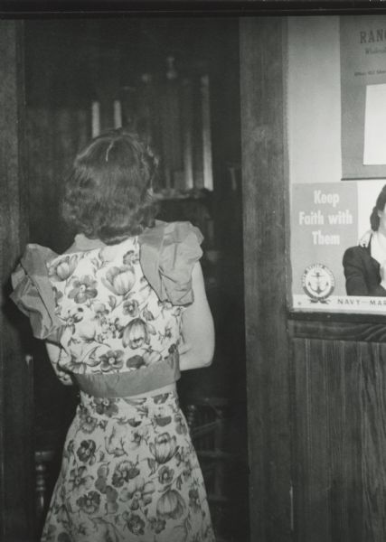 A woman turns her back on an agent as they enter the establishment where she worked at the beginning of a raid on many Hurley area bars. The arrest warrants were for gambling and prostitution.