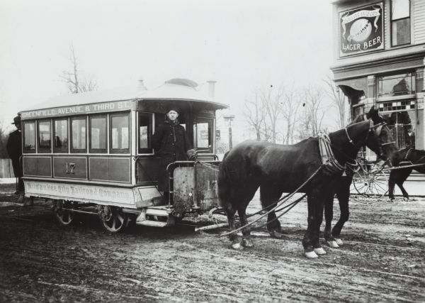 Man driving a horse-drawn trolley of the Milwaukee City Railroad Company on the Greenfield Avenue & Third Street line. The corner of a building advertising Schlitz beer is in the background. Another man stands at the back of the trolley.