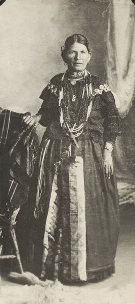 Full-length portrait in front of a painted backdrop of Mrs. Ketch ka mi, daughter of Potowatomi Indian Chief John Young.