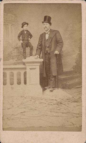 "Carte-de-visite of Major Tot standing on a prop column and wall next to a man of average height in front of a painted backdrop. Both men are holding canes. Major Tot's actual name was Pierre Albert Poitras, born in Fitchburg, Massachusetts in 1869. He was hired by P.T. Barnum and billed as ""The world's smallest perfectly developed man."" He eventually grew to a height of 3.5 feet, weighed ninety pounds and wore a child's size 5 shoe. His father is said to have transported him to engagements in a 14"" satchel. Text on the back reads, ""Big Success Everywhere! Of Major Tot, The Wonderful Human Midget! Age 16 Yrs, Weight Only 10.5 Lbs."""